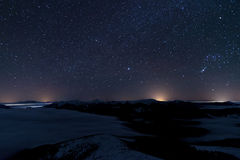 反对深蓝天空的山与在夜间的星 库存图片