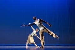 反对深蓝背景的两2位舞蹈家姿势在阶段 免版税库存照片