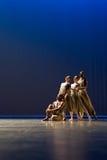 反对深蓝背景的四位舞蹈家姿势在阶段 免版税库存图片