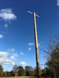 反对深蓝色秋天天空的电话线杆 库存图片
