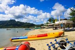 反对清楚的蓝天、山景和水活动性香蕉船的白色沙子海滩 图库摄影