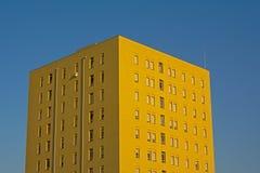 反对清楚的蓝天的黄色公寓楼 库存照片