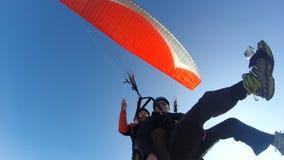 反对清楚的蓝天的滑翔伞 免版税库存照片
