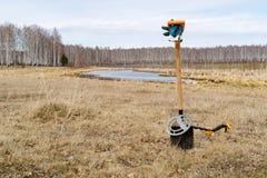 反对湖和领域的背景有在地面的被赌的铁锹在铁锹金属探测器,使sp受伤 库存图片