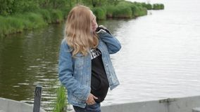 反对湖的背景的怀孕的年轻女人 一个怀孕的女孩走本质上 妇女白肤金发的未来妈妈 影视素材