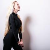 反对演播室背景的美好的性感的白肤金发的妇女姿势 免版税库存图片