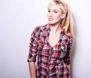 反对演播室背景的美好的性感的白肤金发的妇女姿势 免版税图库摄影