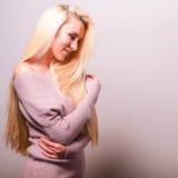 反对演播室背景的美好的性感的白肤金发的妇女姿势 免版税库存照片