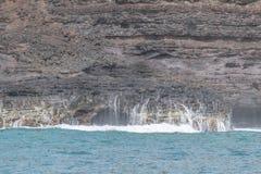 反对灰色熔岩岩石的海洋飞溅 免版税库存照片