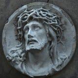 反对灰色石头背景的耶稣基督雕象  免版税库存照片