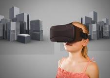 反对灰色背景的女孩与虚拟现实耳机和3D城市大厦 库存图片