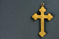 反对灰色背景的老金黄十字架 库存图片