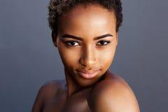 反对灰色背景的肉欲的年轻非洲妇女 免版税库存照片