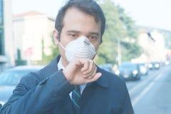 反对烟雾大气污染的人佩带的面具 免版税图库摄影