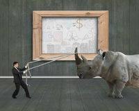 反对犀牛企业概念的商人牵索 库存图片