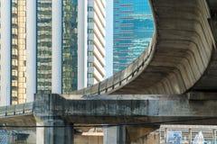 反对现代塔玻璃窗的天空火车铁路桥  免版税库存图片