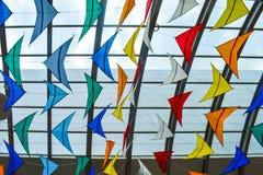 反对玻璃屋顶的许多五颜六色的风筝 库存照片