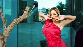 反对玻璃表面的可爱的白肤金发的妇女跳舞在树附近 股票录像
