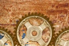 反对生锈的背景的古老嵌齿轮轮子 免版税库存照片