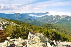 反对用白色云彩盖的小山的大石头 免版税库存照片