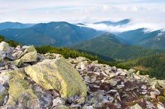 反对用白色云彩盖的小山的大石头 图库摄影