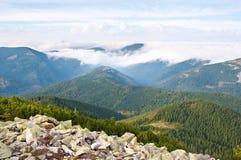 反对用白色云彩盖的小山的石头 库存照片