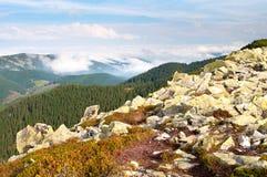 反对用蓬松白色云彩盖的小山的大石头 库存图片