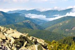 反对用蓬松白色云彩盖的小山的大石头 免版税库存图片
