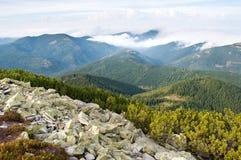 反对用蓬松白色云彩盖的小山的石头 免版税库存照片