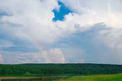 反对白色云彩背景的部份弧彩虹在绿色领域和森林的 库存图片