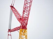 反对白色天空的红色工业建筑用起重机 免版税库存照片