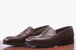 反对白色的时髦的布朗便士游手好闲者鞋子 安置在木反射的表面 库存照片