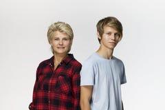 反对白色背景的愉快的家庭、母亲和儿子微笑的画象 免版税库存图片