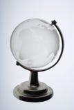 反对白色背景的玻璃地球 免版税图库摄影