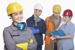 反对白色背景,在微笑的女性建筑工人的焦点的四名建筑工人 免版税库存照片