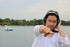反对看照相机的耳机的愉快的年轻人在自然河放松时间 免版税图库摄影