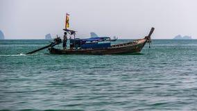 反对石灰石峭壁背景的泰国充气救生艇。 库存照片