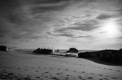 反对碉堡剪影的巨大的水波飞溅在日落天空的在黑白 库存图片