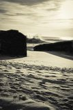 反对碉堡剪影的巨大的水波飞溅在金黄日落天空的在黑白 免版税库存照片