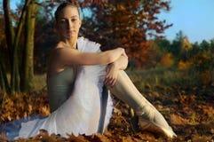 反对秋天森林的芭蕾舞女演员 免版税库存图片