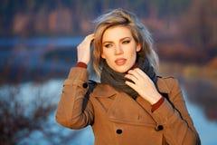 反对秋天自然风景的白肤金发的妇女 免版税库存图片