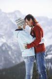 反对积雪的山的爱恋的夫妇 免版税库存照片
