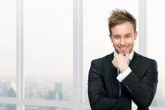 反对窗口的微笑的经理感人的面孔 免版税库存图片