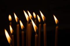 反对窗口的燃烧的蜡蜡烛在一个暗室 免版税库存照片