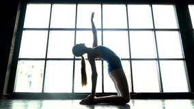 反对窗口背景的女子实践的瑜伽在一个晴天 做瑜伽锻炼的白种人女孩 运动的女孩 影视素材