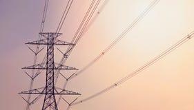 反对紫罗兰色和橙色背景的电定向塔 库存照片