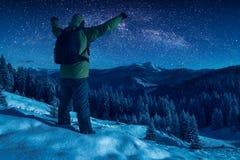 反对繁星之夜天空的远足者 图库摄影