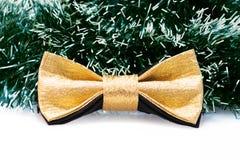 反对绿色圣诞树闪亮金属片背景的欢乐金蝴蝶蝶形领结  免版税库存图片