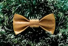 反对绿色圣诞树闪亮金属片背景的欢乐金蝴蝶蝶形领结  库存照片