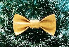 反对绿色圣诞树闪亮金属片背景的欢乐金蝴蝶蝶形领结  免版税库存照片